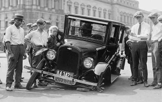 Photograph of an early car with a broken wheel and multiple men overlooking it. The broken healthcare system is pretty much like that broken car: a great deal of repair is needed.