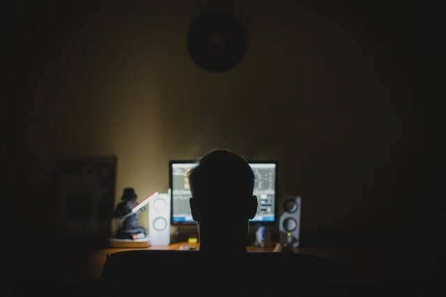 Dark room with a dark figure sitting before a lit computer screen. Private health information is at HUGE risk from hackers. Why are we putting up with ELECTRONIC medical records then?