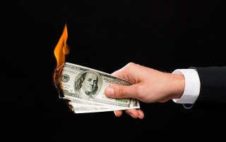 A man's hand holding a few burning hundred dollar notes. Do YOU have money to burn? Does anybody? These healthcare insurance companies made a deal with the devil, and need to deal with the consequences. Cynical play has a price to pay.
