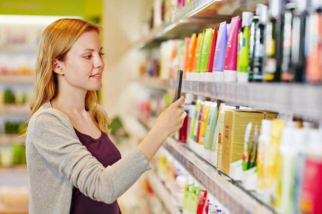 A woman checks over different product labels and presumably prices. Lower your healthcare bills by shopping!