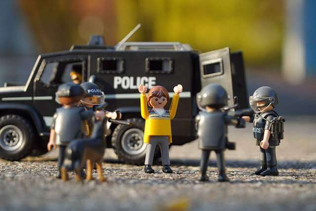 Close up of toy figures; some as police, surrounding one individual who has his hands up. Reliance of politics BREEDS violence not only as initiated by the state, but by the 'served' as well!