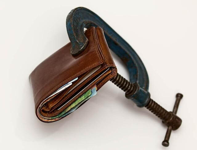 Picture of wallet being squeezed by a vice. These REAL economic laws REALLY do a number to your wallet, among other negative things!