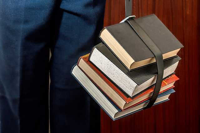 Picture of person holding bundled school books. DON'T GO TO COLLEGE!