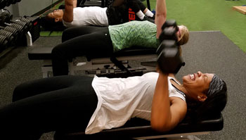 woman exercising with dumbbells in gym