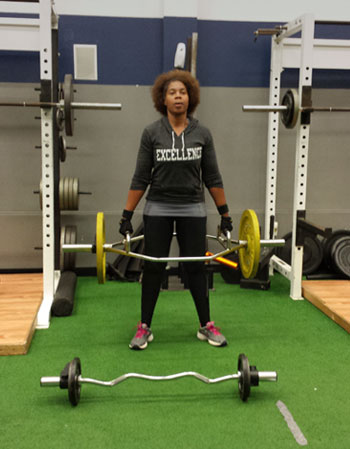 woman exercising with barbell in gym