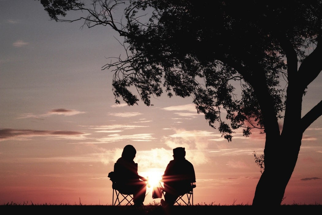 Silhouette of two people sitting in camp chairs beneath a tree as the sun sets in front of them.