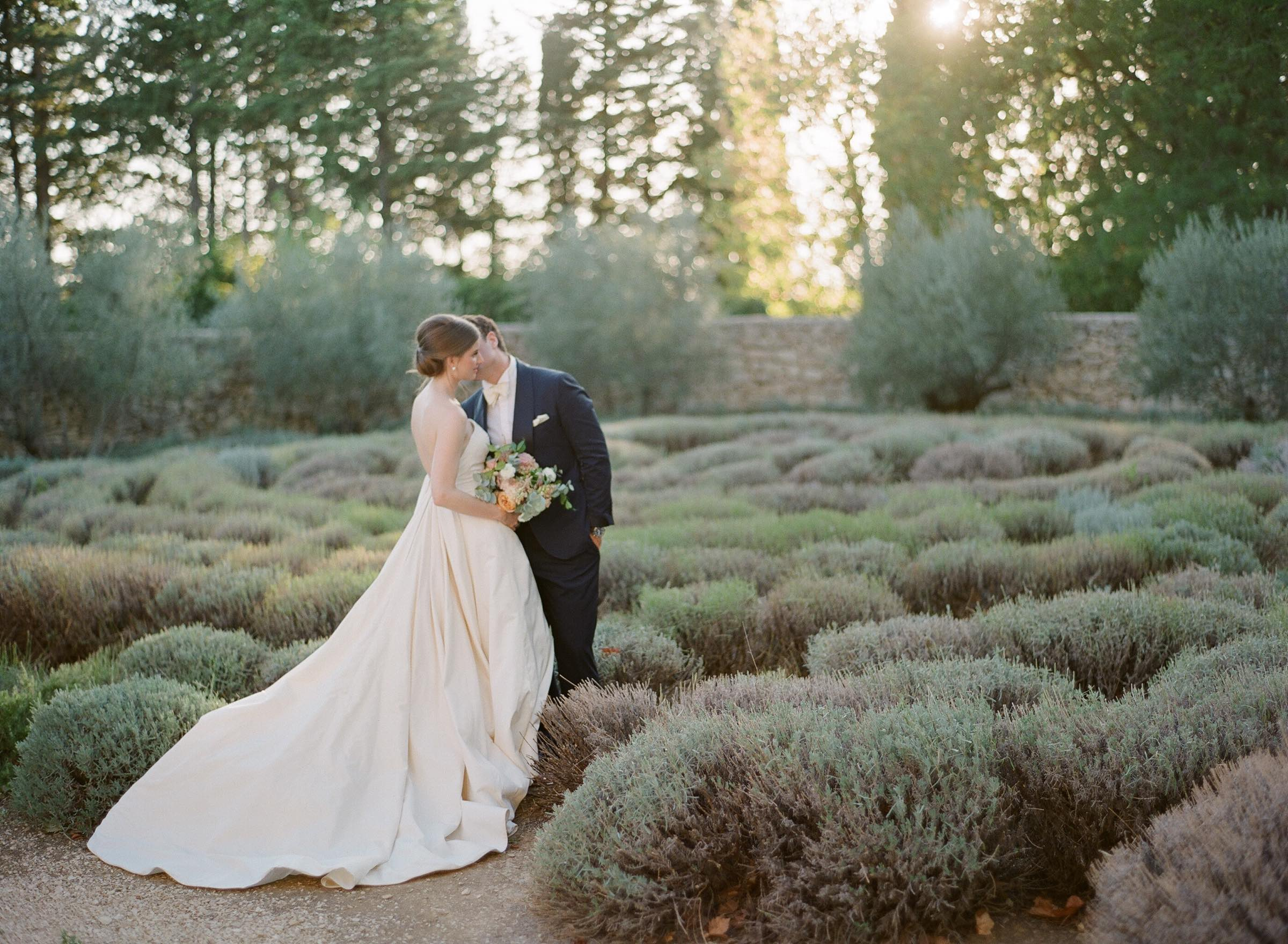 Groom kissing his bride in a middle of a lavender garden