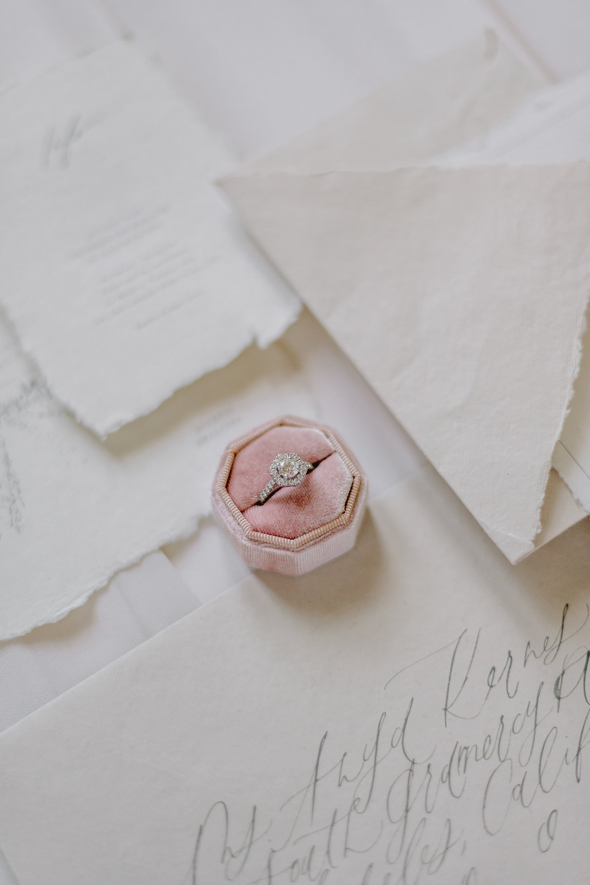 Wedding invitation suite details and wedding ring in a pink velvet box