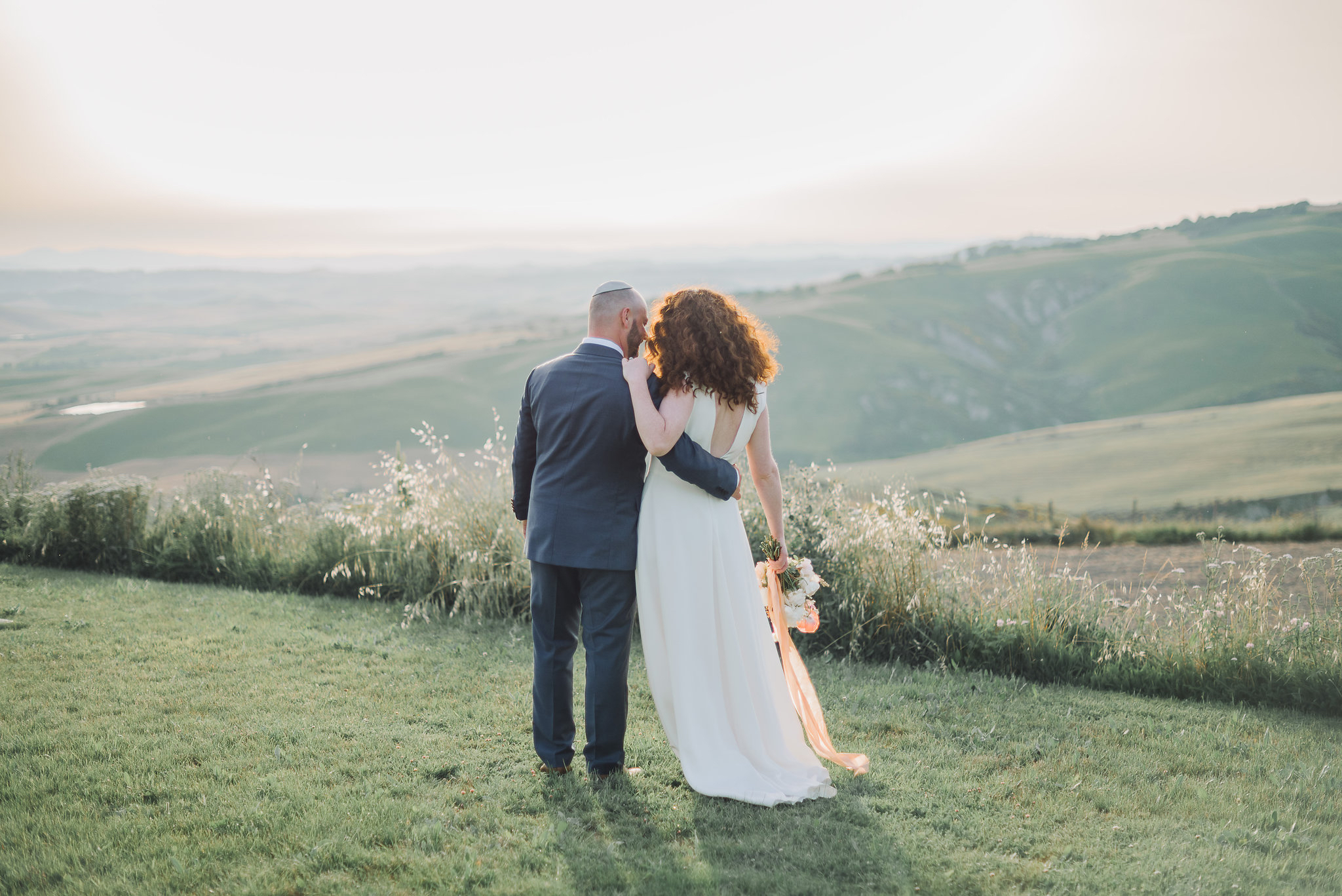Bride and groom looking at the sunset in Tuscany