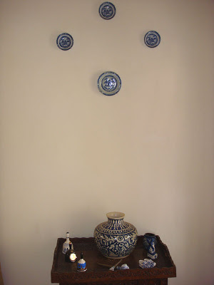 the bell and blue pottery collection displayed on a Kashmiri walnut tea trolley