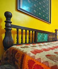 master bedroom, tile inlay on old bed, yellow wall, accent, fabric on wall