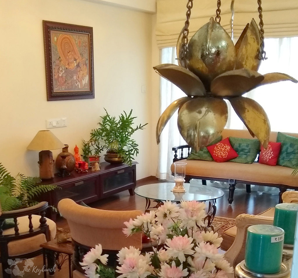 Jayashree Rajan's garden apartment tour on The Keybunch: Living room with mural painting, green plants and brass hanging diya