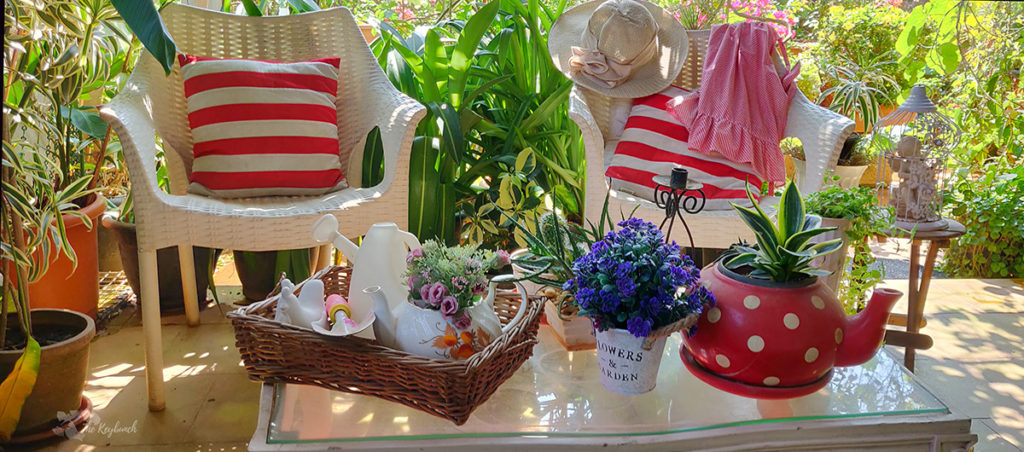 Jayashree Rajan's garden apartment tour on The Keybunch: A Candy striped cushions, red teapot, candle stand, bird cage and flower vase on green garden