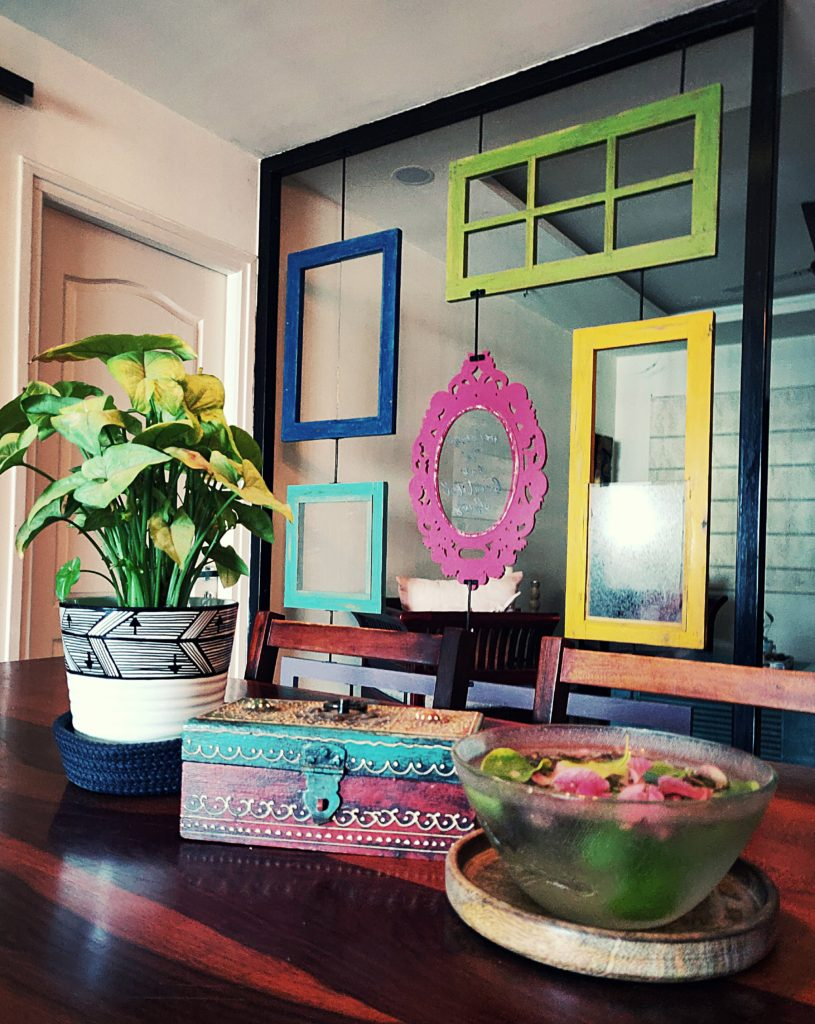 Home style Tour with Rajni in Hyderabad: the dining room is filled with beautiful colorful frames, green plants, mini trunk box and a bowl of fresh flowers