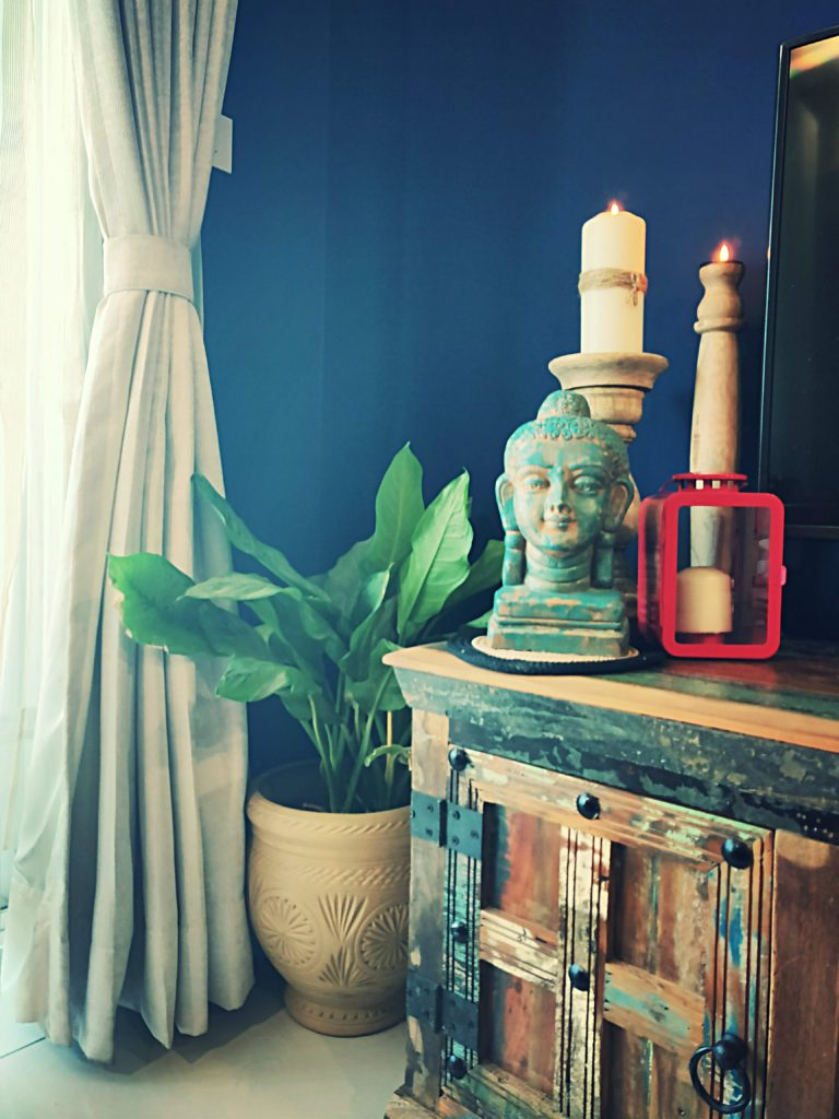 Home style Tour with Rajni in Hyderabad: the collection of buddha statue, candle stands on the drawer and green plants makes the room beautiful