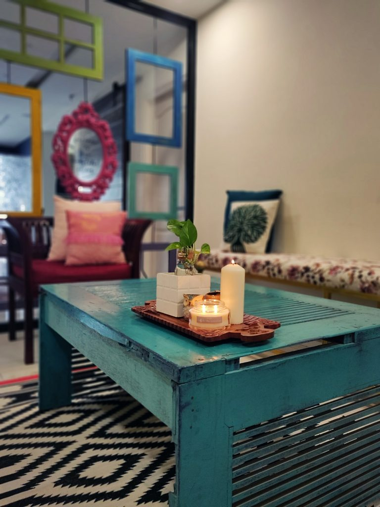 Home style Tour with Rajni in Hyderabad: the living room is filled with beautiful colorful frames, long bench, seater sofa, green plants and candle on table