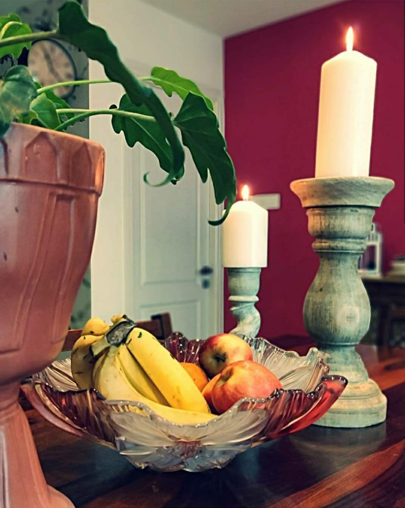 Home style Tour with Rajni in Hyderabad: the dining table filled with green plants, the beautiful candles stand and fresh fruits