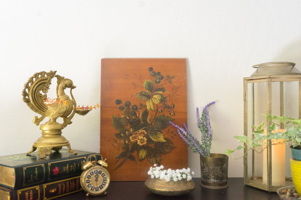 Affinity for antiques home tour of Rushika & Dipkal's - the collection of brass bowl, brass diya, oil painting, candle stand, books and plant at the corner of the room