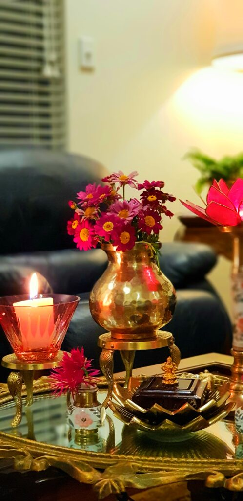 The table in the living room is setting up with fresh flowers, glass candle stand and brass collection on it