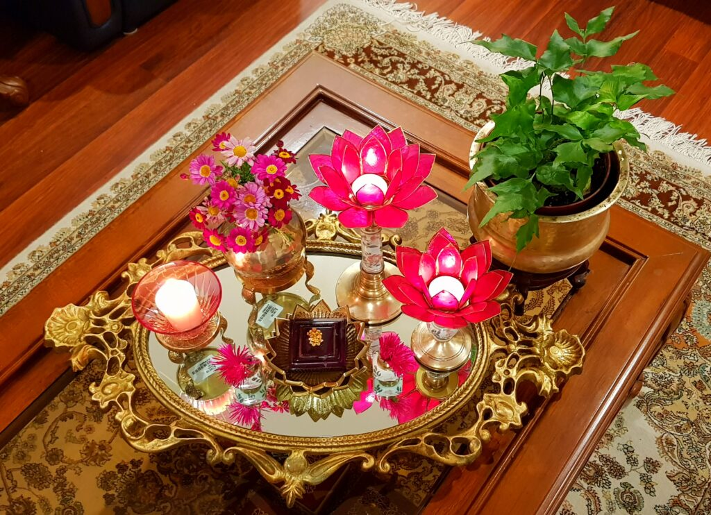 The table in the living room is setting up with fresh flowers, glass candle stand, green plants, lotus candle stand and brass collection on it