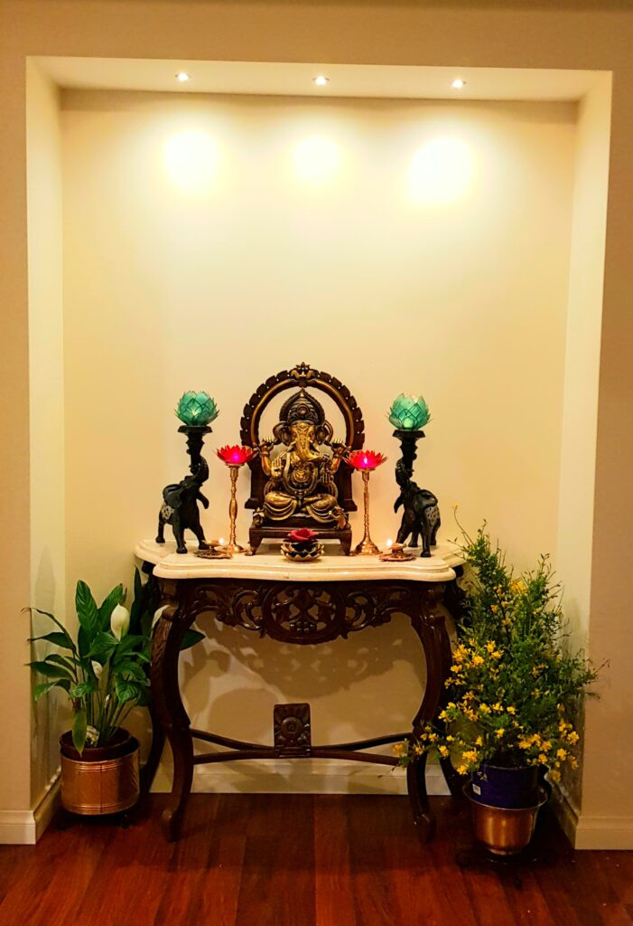 Mixing lotus candles, god ganesha, elephant candle holders, green plants and fresh flowers makes the puja room look bright and beautiful