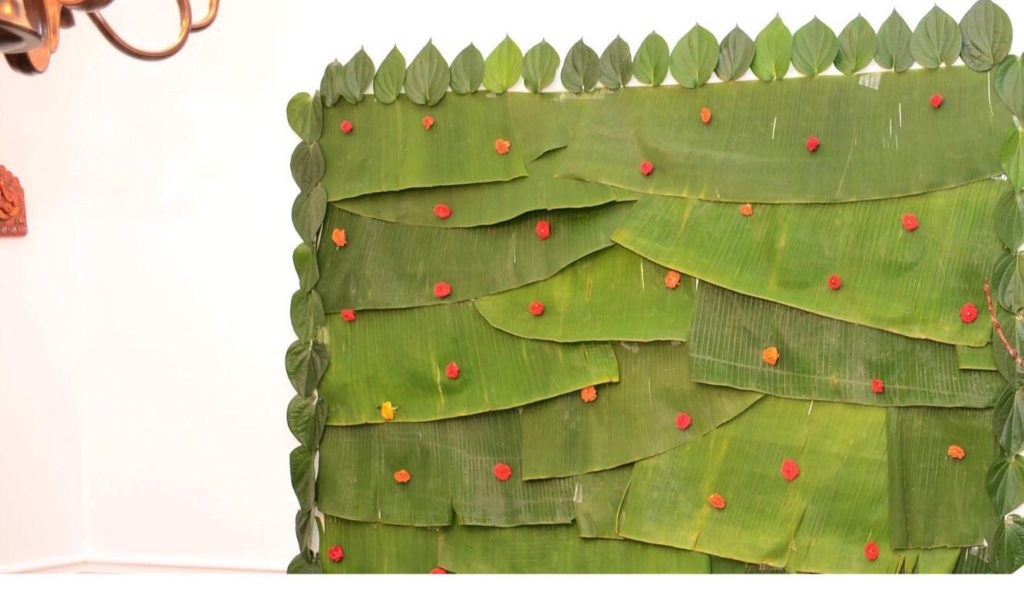 The banana leaf with fresh betel leaves on the sides, decorated on the wall