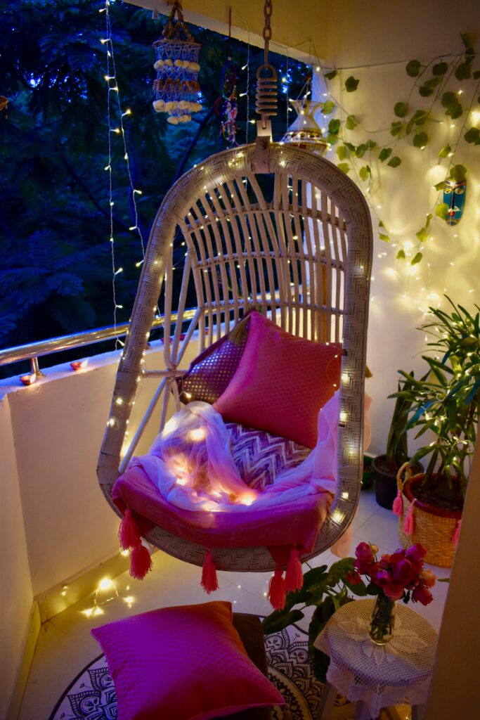 The balcony is decorated with light around the swing chair and Pom-Poms make from wool is used for the shawl swing chair cover and for the jute basket planter.