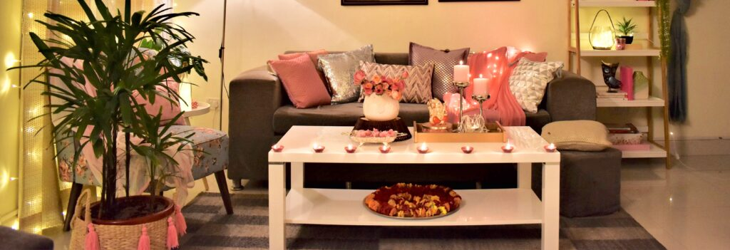 Diwali living room is decorated with pink cushion cover, diyas, and green plants
