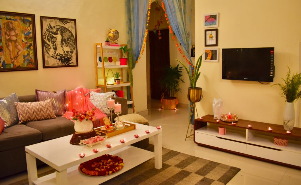 Diwali living room is decorated with pink cushion cover, diyas, wall frame and green plants