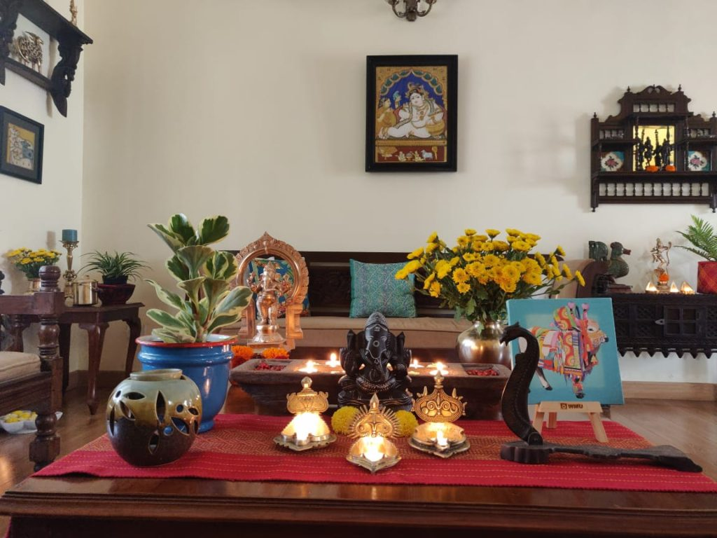 The table at the living room is setting up with fresh flowers, diyas, sculpture, green plants and Pichwai frame