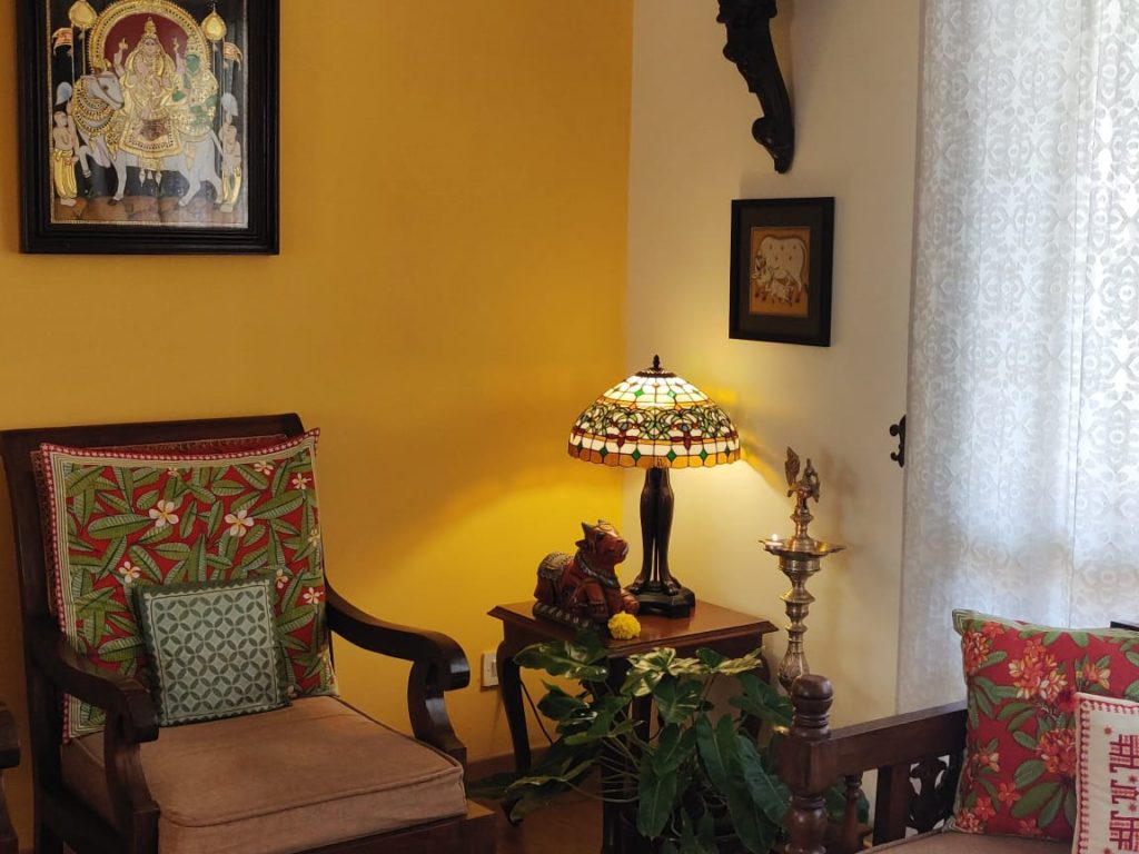 diya brass, lamp, bull sculpture, wall frames and green plants decorated at the corner of the living room