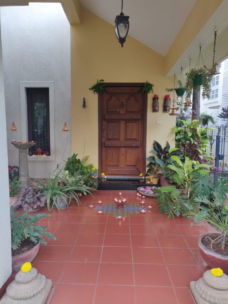 The front door entry is surrounded by green plants, and decorated with rangoli and light diyas for diwali festival
