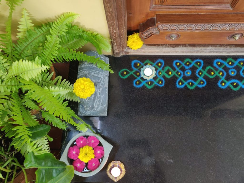 rangoli powder design and fresh flowers rangoli decorated at the front door entry