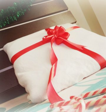 A big red bow wrapped around a pillow, and a mint candy canes