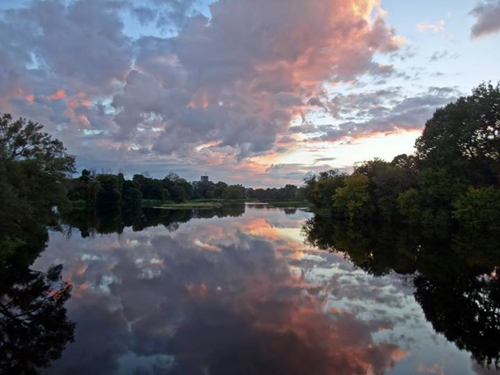At sunset, glowing clouds reflect in the still water of the Rideau River.