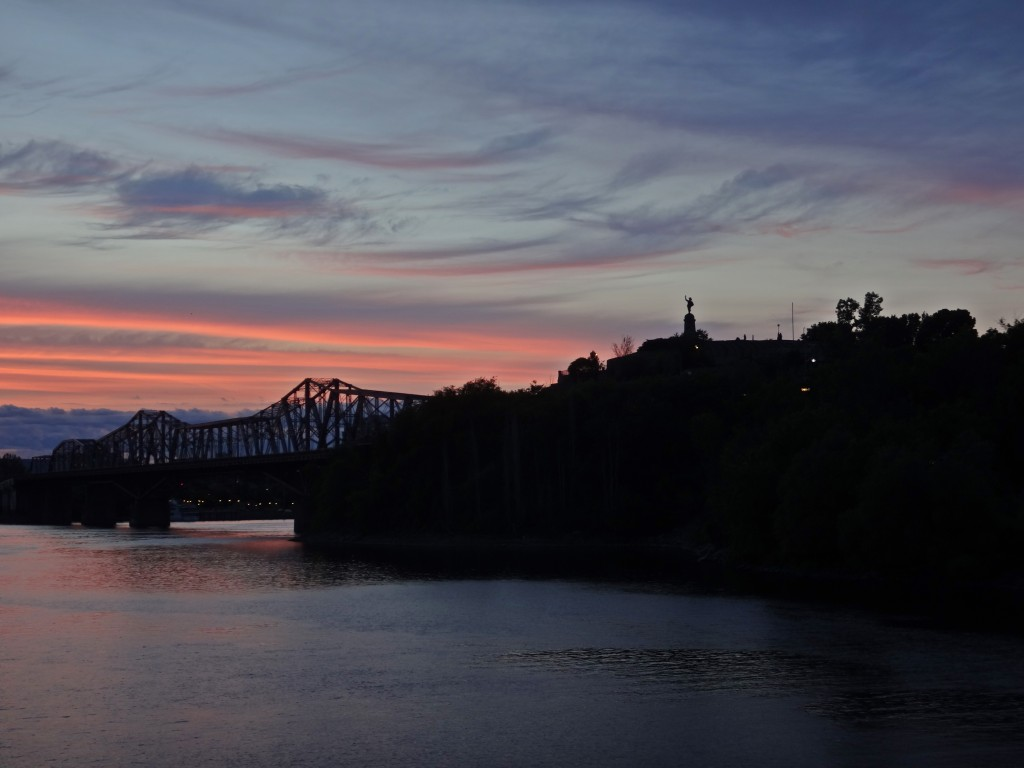 The Alexandra Bridge and Statue of Samuel de Champlain stand silhouetted against wispy blue clouds and glowing pink bands of the dusk sky.
