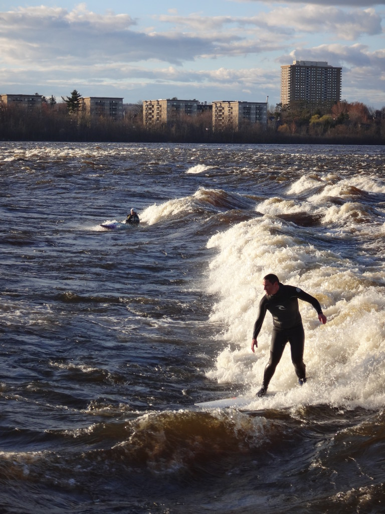 "A surfer and a kayaker Ride ""The Wave"" at Bate Island"