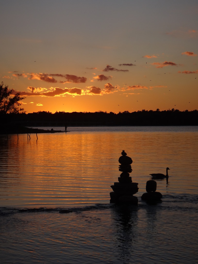 In the foreground, a balanced stone sculpture and a goose stand silhouetted against the glowing water of the river, while a fisherman stands in silhouette on a point in the distance.