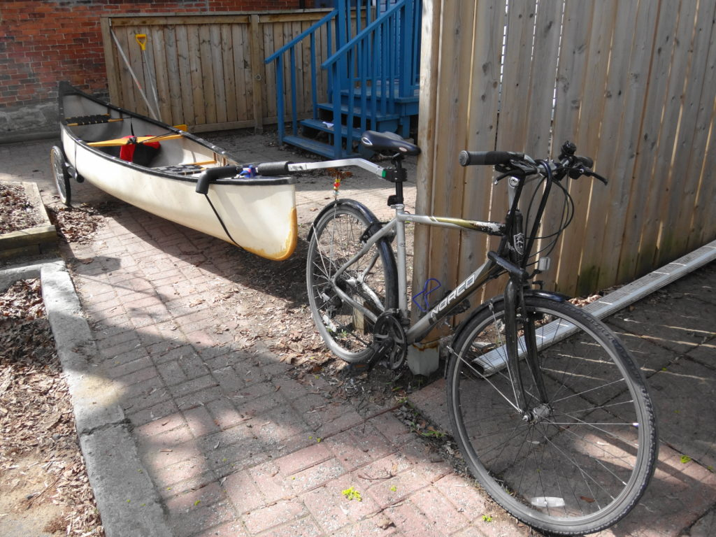 A canoe rides on a trailer attached to a bicycle.