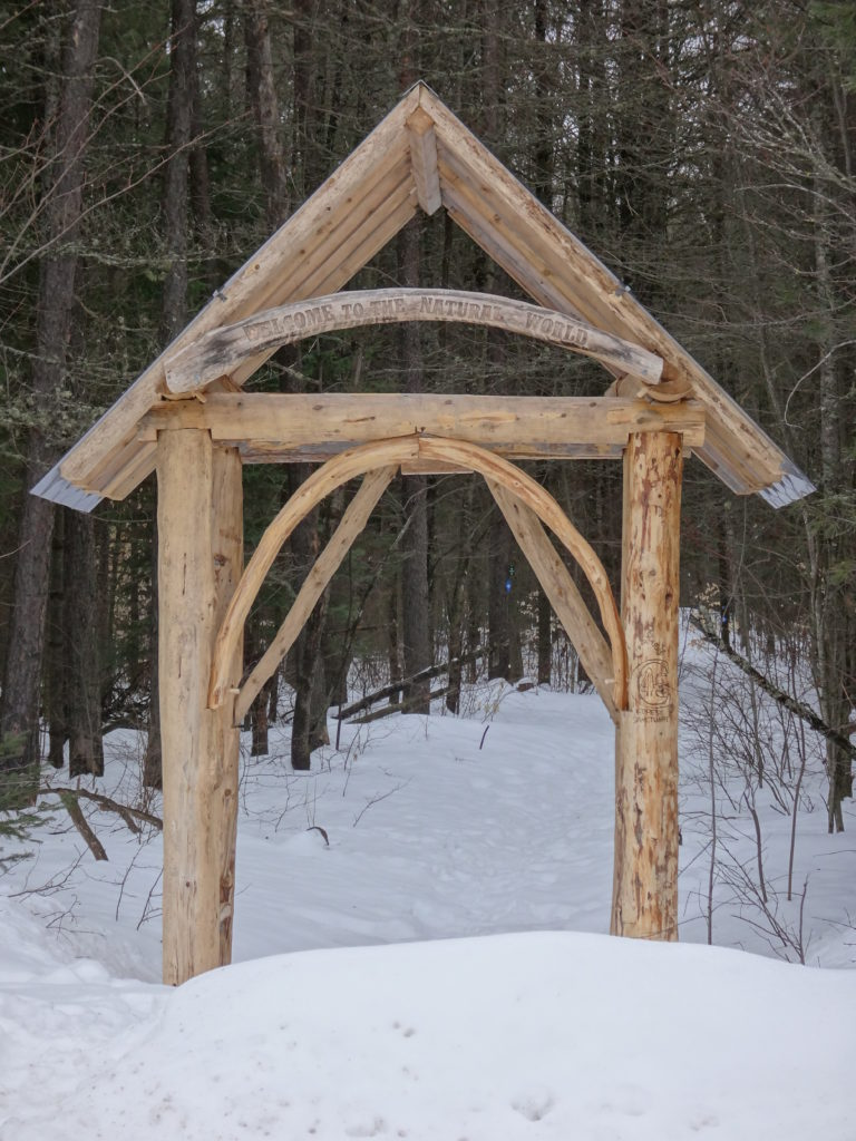 A wooden archway spans an entrance to the Four Seasons Conservation Forest trail network.
