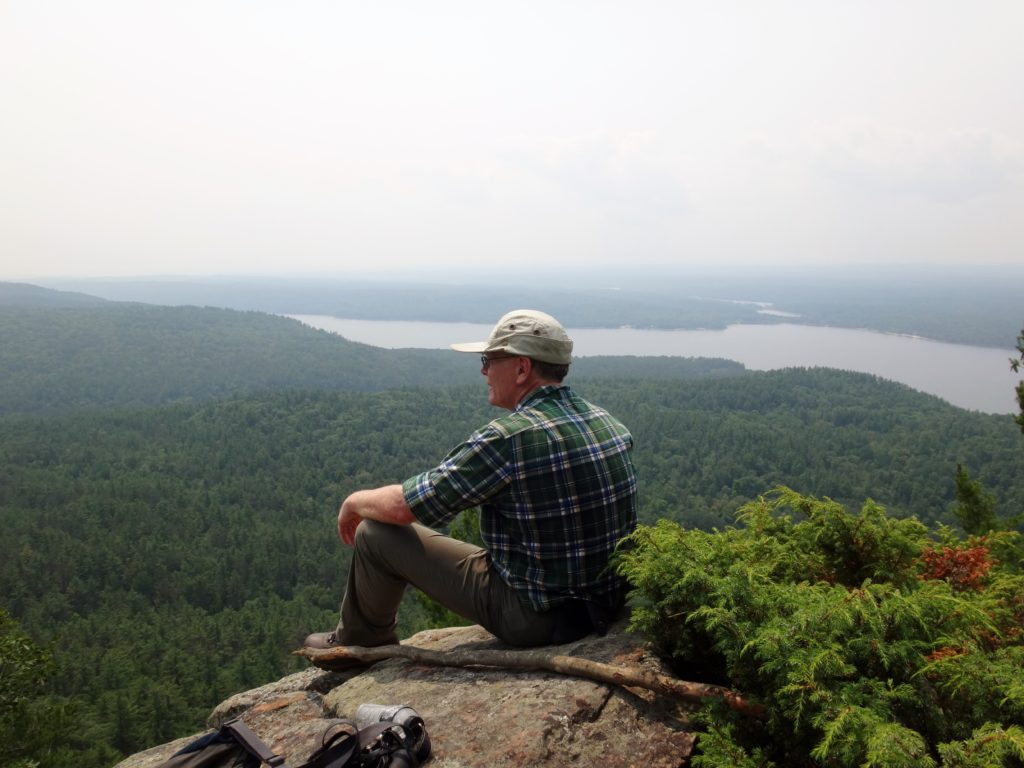 The author rests on a rocky lookout at the top of Mount Martin, with forest and the Ottawa River in the background.