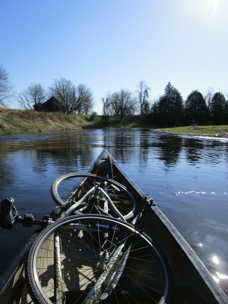 A bicycle and canoe trailer are packed in the bow of a canoe, which is pointed downstream on the flat water of the Jock River..