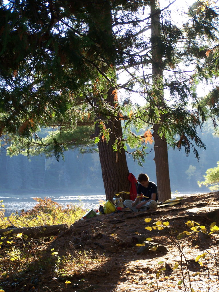 A boy sits under a tree with the Barron River in the background.