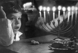 Photo of young child and lit menorah.