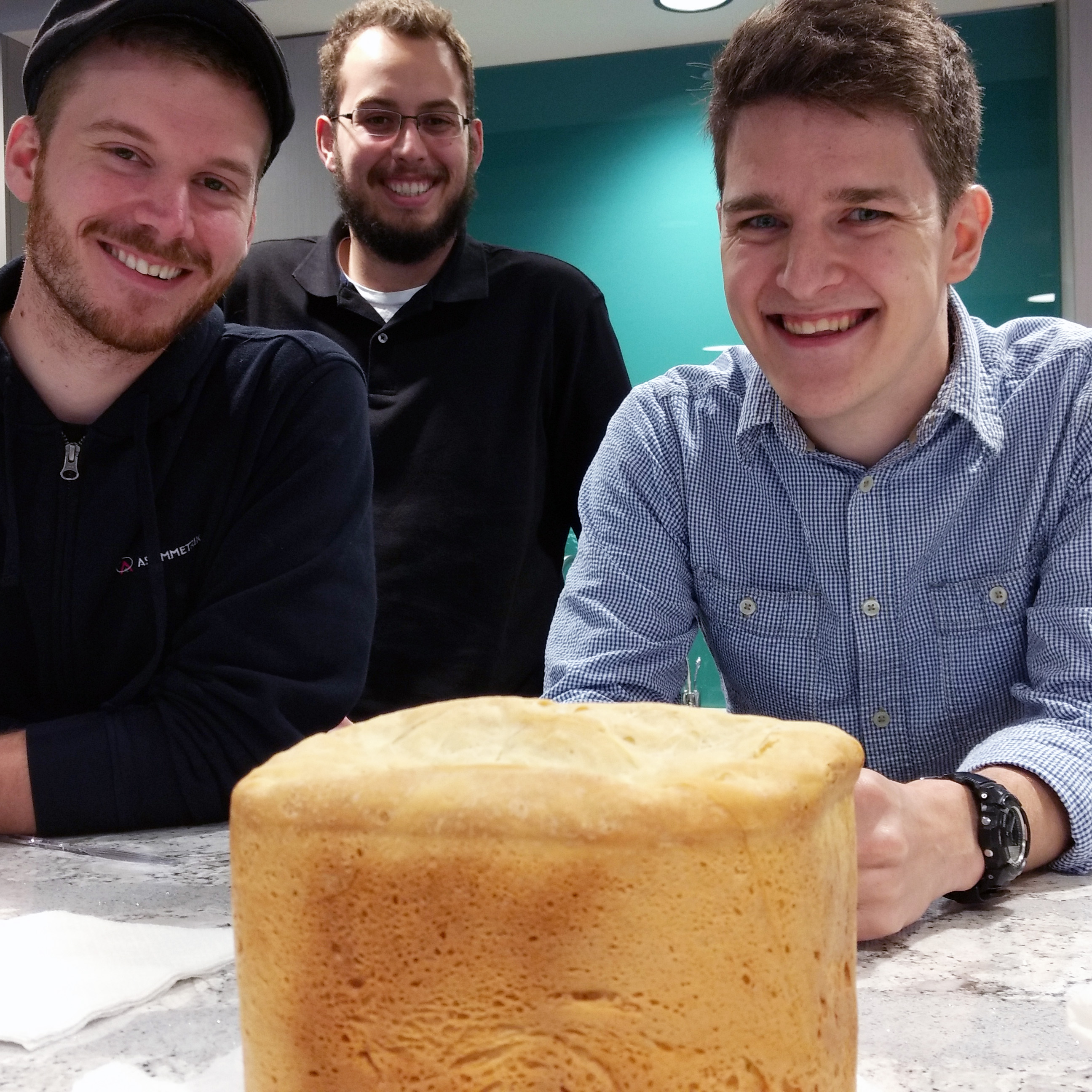 Three Men with loaf of bread in office kitchen