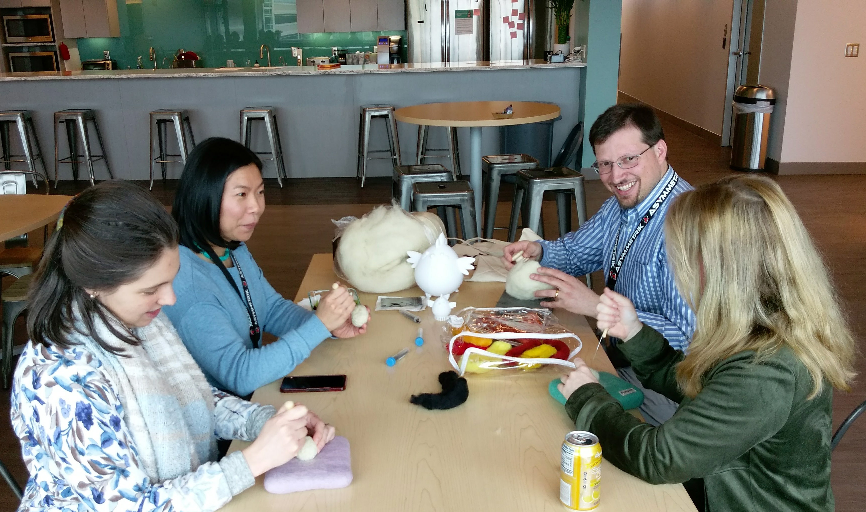 office employees sitting at table needle felting crafting three women one man