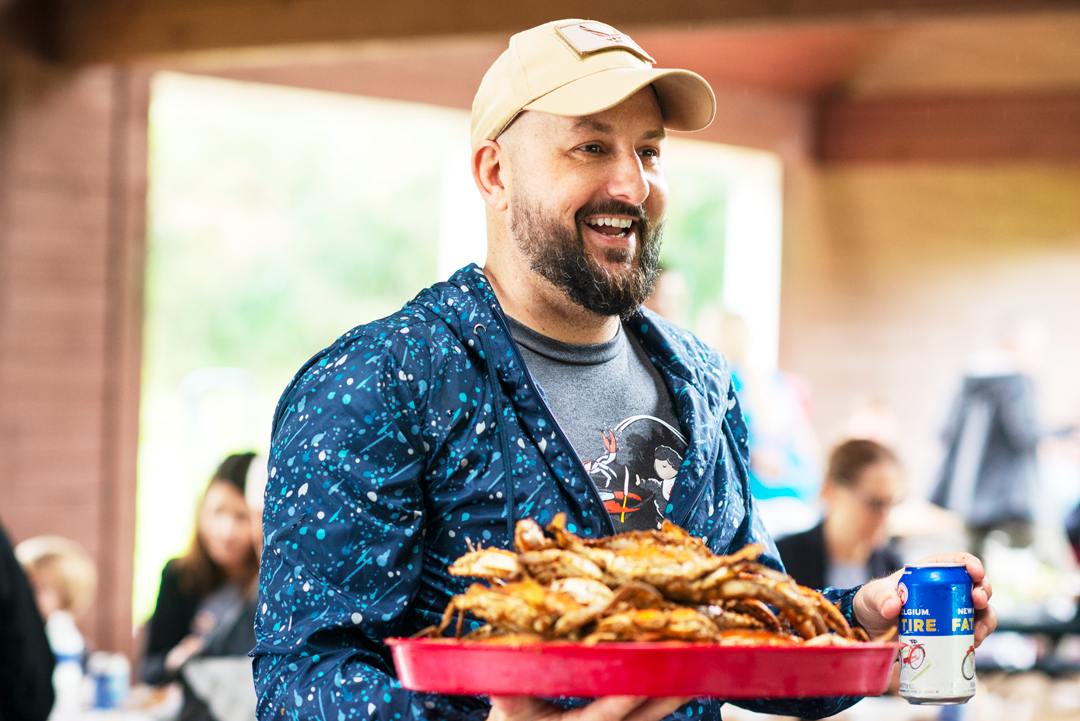 man holding crabs and beer at crab feast