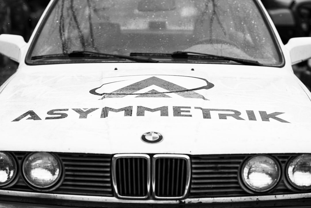 black and white BMW 30 rallycar with Asymmetrik logo
