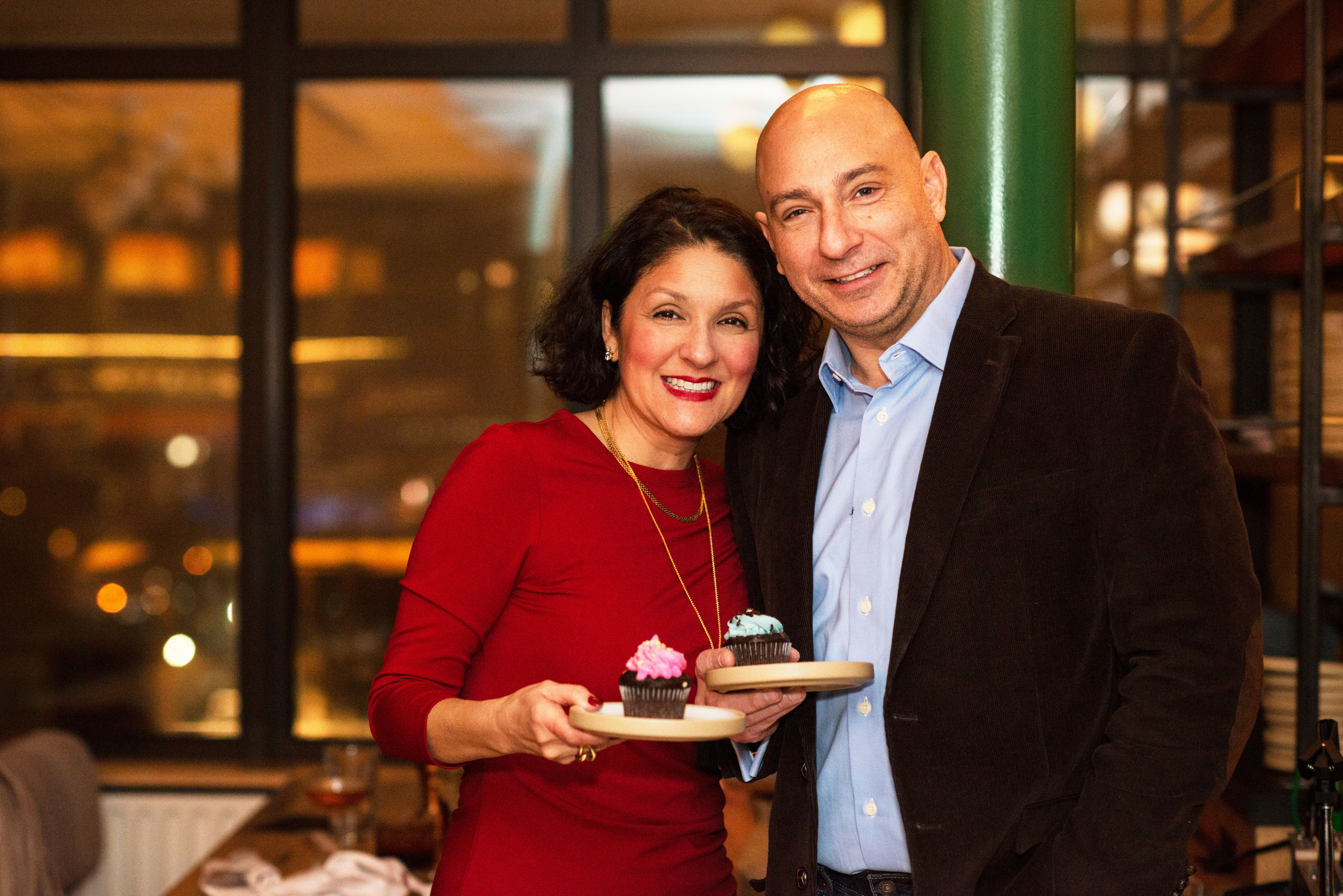 man and woman in red dress posing with cupcakes on plates