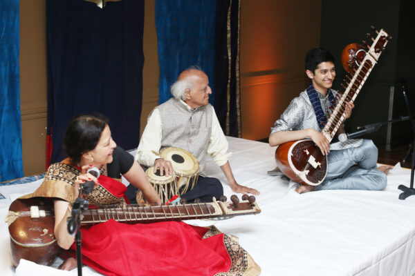 two men and one woman playing sitar